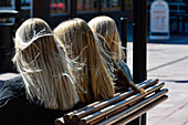 Four young women with typically Swedish blonde hair sit on a bench, Mora, Dalarna, Sweden
