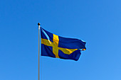 The flag of Sweden flutters in the wind against a beautiful blue sky, Bjuröklubb, Västerbottens Län, Sweden