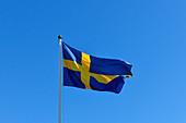 Die Flagge von Schweden flattert im Wind vor herrlich blauem Himmel, Bjuröklubb, Västerbottens Län, Schweden