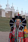 Eine mongolische Frau in historischer Tracht vor der Mauer mit Stupas, die das Kloster Erdene Dsuu umgeben, Kharakhorum (Karakorum), UNESCO-Weltkulturerbe, Mongolei