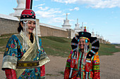 Mongolian women dressed in historic costume in front of the wall with stupas surrounding the Erdene Zuu monastery in Kharakhorum (Karakorum), a UNESCO World Heritage Site in Mongolia.