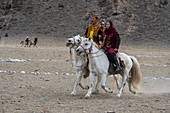 A couple at the Kyz Kuar (Catch up with a girl) game, a traditional horseback riding game were the boys being whipped by the girls if the girl can catch the boy; at the Golden Eagle Festival near the city of Ulgii (Ölgii) in the Bayan-Ulgii Province in western Mongolia.