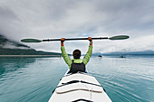 Sea kayaker extends paddle over her head, pristine waters of Muir Inlet in distance, Glacier Bay National Park, Alaska
