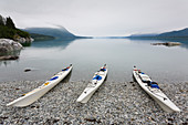Sea kayaks on a remote beach, calm waters of an inlet on the Alaska coastline.