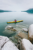 Female sea kayaker paddling pristine waters of Muir Inlet, overcast sky in distance, Glacier Bay National Park, Alaska