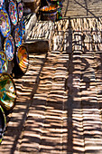 Shadows and shade patterns falling on a pavement, pottery bowls on display