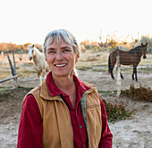Mature woman at home on her property in a rural setting, horses in a paddock