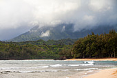 A sandy beach and waves breaking on shore, mountains in the mist above.