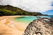 Laval rocks and headland on a Hawaiian coastline and a sweeping sandy beach.