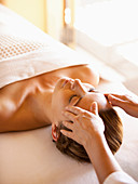 Woman lying on massage table receiving facial massage at a luxury spa in Napa Valley California