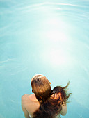 Rear overhead view of woman in water in swimming pool of a luxury resort in California