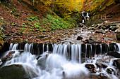 Ukraine, Zakarpattia region, Carpathians, Verkhniy Shypot waterfall, Blurred waterfall in autumn woods