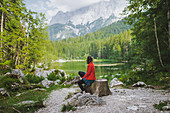 Germany, Bavaria, Eibsee, Woman sitting by?Frillensee?lake