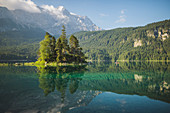 Germany, Bavaria, Eibsee, Distant view of woman paddleboarding on the lake Eibsee in Bavarian Alps at sunrise