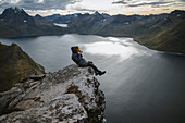 Norway, Senja, Man taking photo sitting on edge of steep cliff on top of mountain Segla
