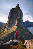 Norway, Senja, Man standing in front of Segla mountain at sunrise