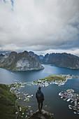 Norway, Lofoten Islands, Reine, Man looking at fjord from Reinebringen mountain