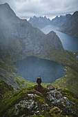 Norway, Lofoten Islands, Reine, Man on Reinebringen mountain with lake and fjord in background