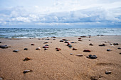 Baltic beach with washed up stones after a storm, rough sea and cloudy sky, Usedom, Mecklenburg-Western Pomerania, Germany