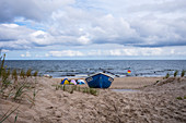 Old fishing boat on the beach in Bansin. Windy day with slightly wavy cloudy sky and tents on the beach, Usedom, Mecklenburg-Western Pomerania, Germany