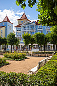 Park with benches in front of old villas on the beach promenade in Zinnowitz with tourists, Usedom, Mecklenburg-Western Pomerania, Germany