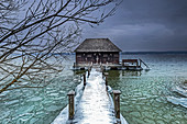 Winter morning on Lake Starnberg, snow-covered jetty with boat hut, Bernried, Bavaria, Germany