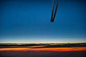Airplane with contrails just before sunrise