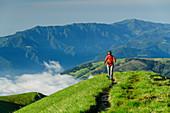 Frau beim Wandern steigt über Wiesenrücken zum Monte Pavione auf, Monte Pavione, Belluneser Dolomiten, Venezien, Venetien, Italien