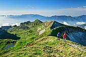 Man and woman hiking up over meadow ridge to Monte Pavione, Monte Pavione, Belluno Dolomites, Belluno Dolomites National Park, UNESCO World Heritage Dolomites, Veneto, Veneto, Italy