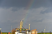 A rainbow behind a fishing cutter on the North Sea, Duhnen, Cuxhaven district, Lower Saxony