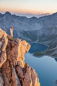 Photographer on a cliff above Lünersee, Brandnertal, Vorarlberg, Austria