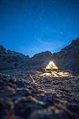 Starry night over the illuminated Boarelli bivak on way to Monviso, Valle Varaita, Cuneo province, Piedmont, Italy