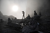 Silhouette of photographer standing in the mist at Cameraccio Pass, Valmasino, Valtellina, Sondrio province, Lombardy, Italy