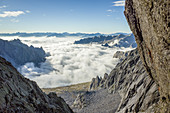 Val Masino in a sea of clouds view from Porcellizzo Pass, Sondrio province, Valtellina, Lombardy, Italy\n