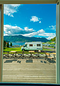 Window view of the campground: campervans, rvs and tents, people enjoying their holidays in Norway