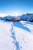 Fußabdruck im Neuschnee mit traditioneller Hütte im Hintergrund, Soglio, Bergell-Tal, Kanton Graubünden, Schweiz, Europa