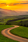 Winding road over the hills at sunset,Canton of Appenzell, Alpstein, Switzerland, Europe
