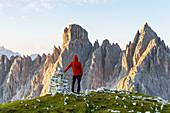 Italy,Veneto,Belluno district,Auronzo di Cadore,a man contemplates the sunrise on the Cadini di Misurina group