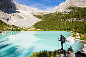 Italy,Veneto,Belluno district,Cortina d'Ampezzo,hiker admires the turquoise water of Lake Sorapis