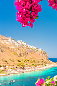Turquoise sea color at Limeni framed by purple blooming flowers, Mani region, Peloponnese, Greece, Europe
