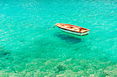 Wooden boat floating on the crystal and turquoise sea at Limeni, Mani region, Peloponnese, Greece, Europe