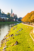 Tourists relaxing along Salzach river, Salzburg, Salzburger Land, Austria, Europe