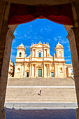 Tourist climbing the stairs of St nicholas church cathedral of Noto, Siracusa province, Sicily, Italy