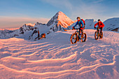 Fat bikers in high mountains at sunrise. Cevedale mount, Valfurva, Sondrio district, Lombardy, Italy.