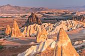 Sunrisescape of Tuff rock formations in Cappadocia. Rose valley, Goreme, Capadocia, Kaisery district, Anatolia, Turkey.