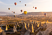 Hot air balloons between the rock tuff formations of Goreme. Capadocia, Kaisery district, Anatolia, Turkey.
