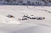 Alpine huts in the snow during winter. Rezzalo valley, Sondalo, Valtellina, Sondrio district, Lombardy, Alps, Italy, Europe.