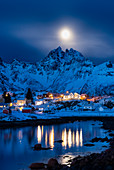 The small village of A, the lasf of Lofoten island by night. With moonlight and mountain peaks in background. A, Lofoten Island, Norway, Scandinavia, Europe.