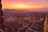 Elevated cityscape of Bologna old town from Asinelli tower during sunset with San Luca church in the background. Bologna, Emilia Romagna, Italy, Europe.