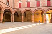 Tourist admiring Accursio palace interior courtyard. Maggiore square, Bologna, Emilia Romagna, Italy, Europe.